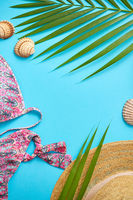 Women beach summer clothes and accessories collage on blue background