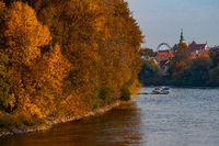 View over river with sports boats and colorful autumn trees with old town of Regensburg with ferris wheel in background n warm sunny october day