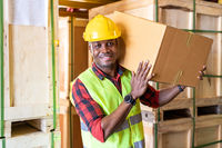 Portrait of Afican Black warehouse worker hold box.