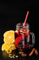 Mulled wine in a glass mug with fruits and spices