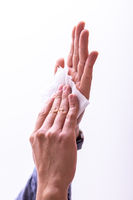 Man cleaning hands with wet wipes