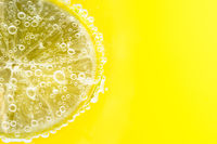 Fresh cut lemon in soda water with bubble on yellow background. Healthy commercial fruit photography.