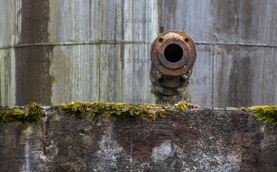 The tank nozzle on the old concrete wall