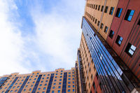 Windows of a high multi-storey residential building. Residential apartment building. Blue sky. Place under the text. . An article about housing. Russia, St. Petersburg April 21, 2020