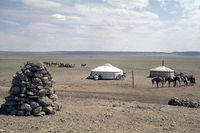 Yurts and pets of Mongolian Arates in the Gobi desert, in the foreground an Ovoo, photo 1977