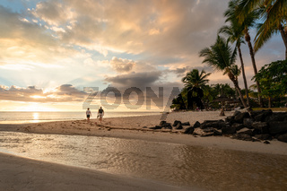 A couple walking on the beach at sunset