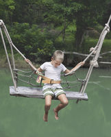 Boy swinging on a swing over the river
