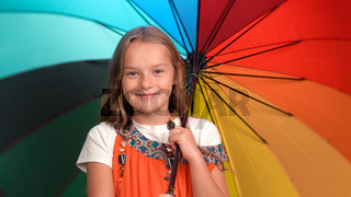 Smiling girl in mother's sundress with beads holds open bright multi-colored umbrella. Caucasian child looks at camera and smiles