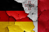 flags of Germany and Malta painted on cracked wall