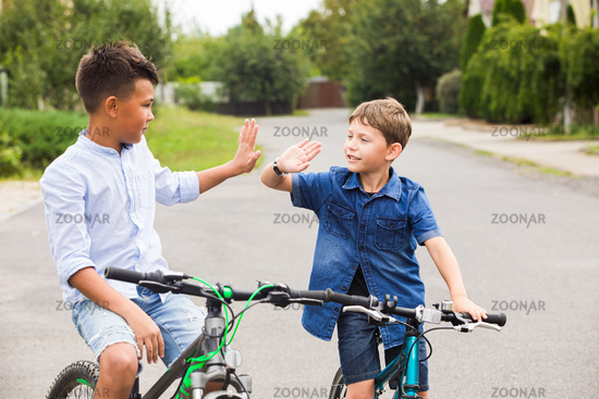 The friends on bicycles greet each other on the street