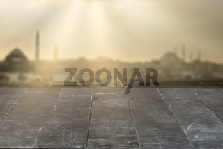 Old wooden dark grey table for display your products on a blurred cityscape background.