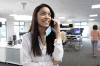 Businesswoman talking on smartphone using smartphone at modern office