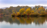 Colorful trees in the mist at a small lake in Bavaria, Germany in autumn