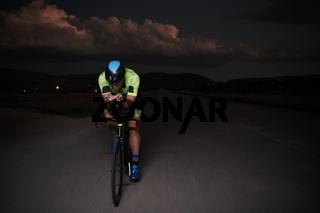 triathlon athlete riding bike fast  at night