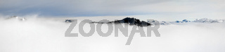 Winter Panoramic View to snow covered mountains above the clouds of inversion fog. View from Riedberger Horn in Allgau, Bavaria, Germany.