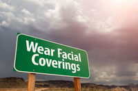 Wear Facial Coverings Green Road Sign Against Ominous Stormy Cloudy Sky