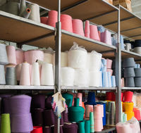 Spools with different color thread at knitting factory