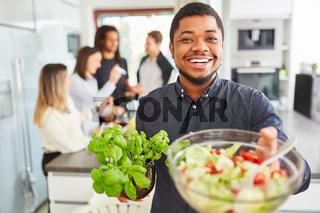 Afrikanischer Mann mit Salat und Basilikum in WG Küche