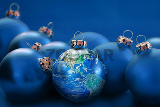 earth globe as christmas ball between blue baubles, metaphor universal peace, environmental protection,