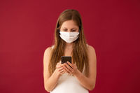 Woman in face mask texting on mobile phone with red background