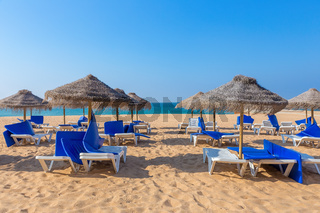 Wicker parasols and beach beds at coast with sea