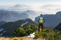 Man hiking on mountain trail. Great view above the clouds and fog.