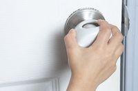 A kid trying to open the door with a child Proof Door Knob Covers over doorknob.