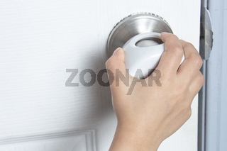 A kid trying to open the door with a child Proof Door Knob Covers over doorknob.
