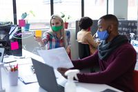 Two diverse business people wearing face masks in creative office