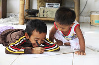 Children of an Indonesian artist paint while sitting on the floor. Bali