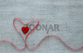 Valentine's day background with red heart ribbon isolated on gray cloth background.