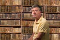 Senior caucasian man sitting in library full of old books on shelves