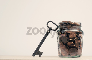 Cent and Euro coins in a canning jar, next to it is a large key, concept for success, savings and retirement