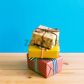 Colorful gift boxes on wooden table with blue background