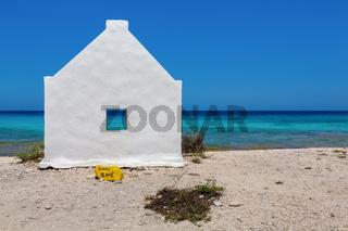One white slave house on beach near blue sea