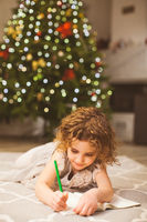 Christmas holidays and childhood concept with girl, writing on a floor