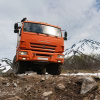 Russian off-road expedition passenger truck KamAZ on mountain road on background of volcano