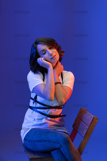 Brunette woman posing in Studio isolated on blue background. Young model illuminated with pink neon light