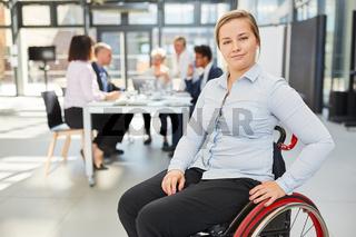 Stolze Geschäftsfrau im Rollstuhl vor ihrem Team