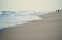 Incidental people walking along the beach of Atlantic Ocean. USA