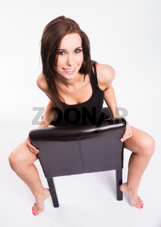 Stunning Young Beautiful Barefoot Woman Straddles Black Leather Chair