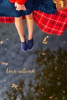 Legs of a young girl near the lake on a plaid in a red cage. Beautiful reflection in the water. View from above. The inscription love autumn.