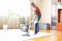 Grandmother and granddaughter cleaning room together