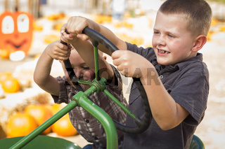 Adorable Young Boys Playing on an Old Tractor Outside
