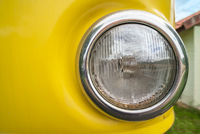 Round headlight of an old yellow car