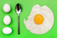 White eggs and spoon on a green background. Breakfast concept, soft-boiled egg. International cuisine, food. Top view, copy space.