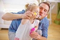 Vater und Tochter pusten gemeinsam Seifenblasen