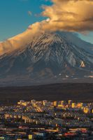 Evening view from above of Petropavlovsk-Kamchatsky City at sunset on background active volcano