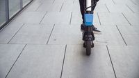 Closeup of a man riding electric scooter