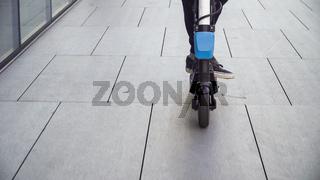 Closeup of a man riding electric scooter